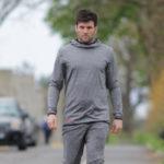 Homme en tenue de sport grise dans une rue